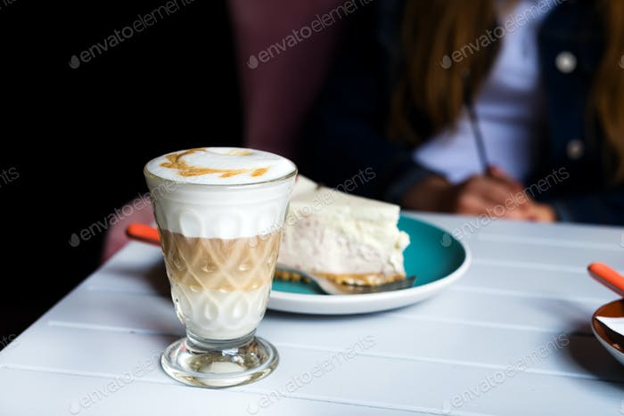 Glass of Latte macchiato with rich milk foam in cafe