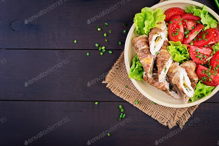 Köstliche Hähnchenbrötchen gefüllt mit Käse und Spinat in Speckstreifen gewickelt. Ansicht von oben