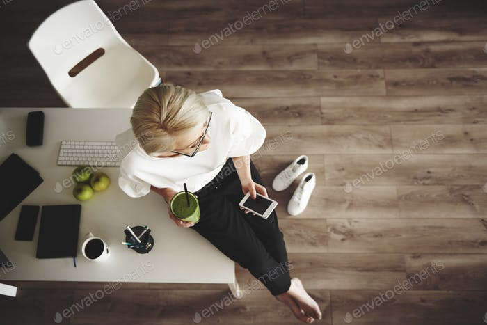 Smart businesswoman with smoothie and smartphone sitting at desk