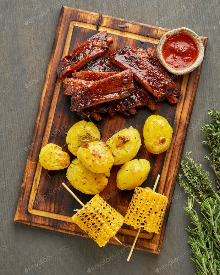 Spicy barbecue pork ribs, corn ears and crushed smashed potatoes. Slow cooking recipe