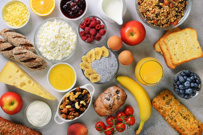 Healthy breakfast ingredients, food frame. Granola, egg, nuts, fruits, berries, toast, milk, yogurt