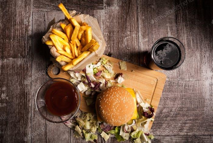 Deliciosas hamburguesas hechas en Página de inicio en plato de De madera junto a papas fritas y co