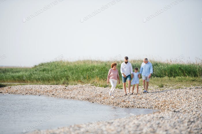 Multigeneration family on a holiday walking by the lake, holding hands.