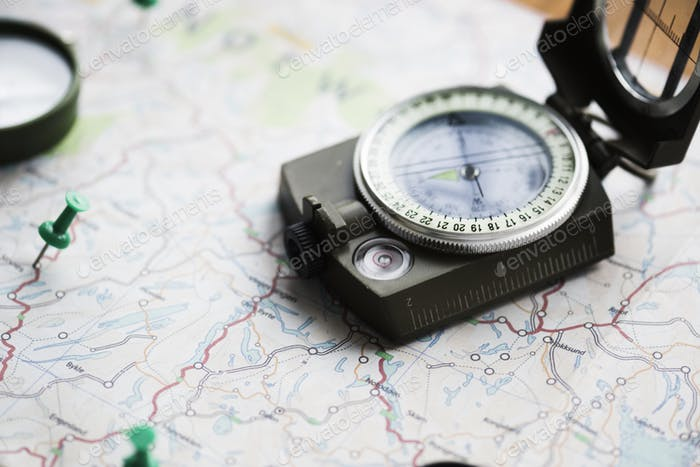 Closeup of compass on the map journey planning