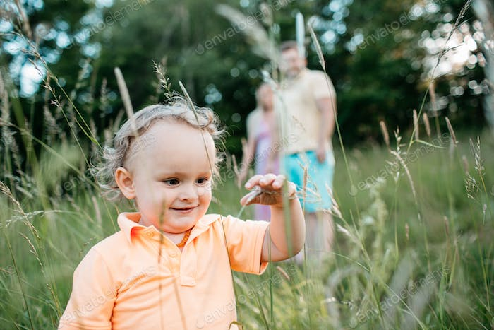 A happy little child touching grass stems.