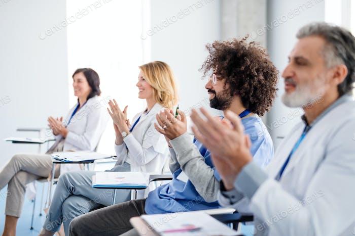 Grupo de médicos escuchando la presentación de la conferencia médica.