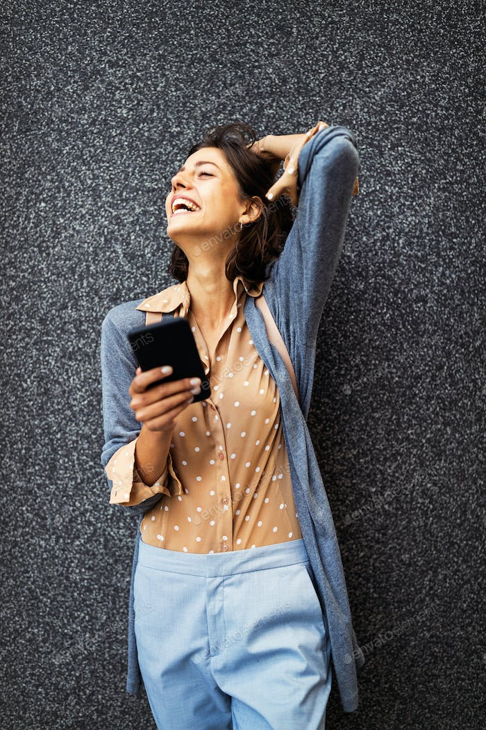 Young beautiful happy woman using smart phone