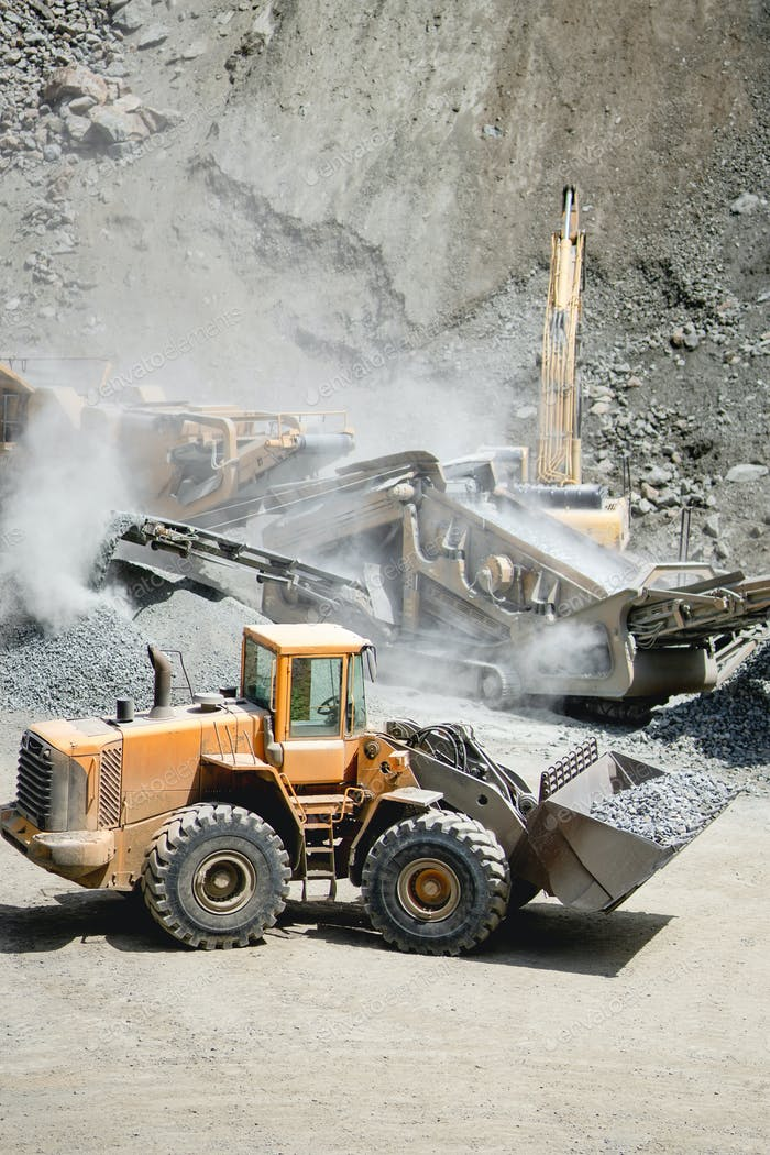 Industrial heavy duty large wheel loader moving gravel on highway construction site