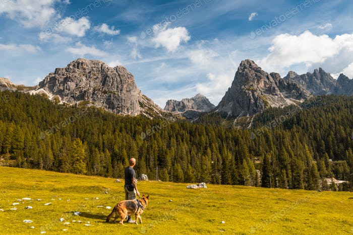 Active Man hiking with Dog in Dolomites Mountains
