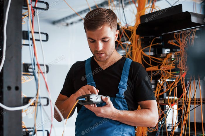 Young man in uniform with measuring device works with internet equipment and wires in server room