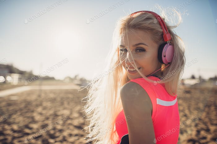 Portrait of young beautiful woman listening to music at beach. Close up face of smiling blonde woman