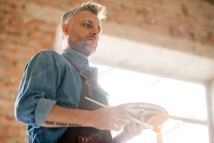 Pensive or serious middle aged man in workwear thinking of ideas at work