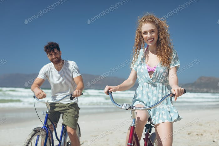 Young couple riding bicycle at beach on a sunny day