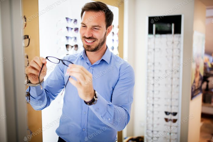 Health care, eyesight and vision concept - happy man choosing glasses at optics store