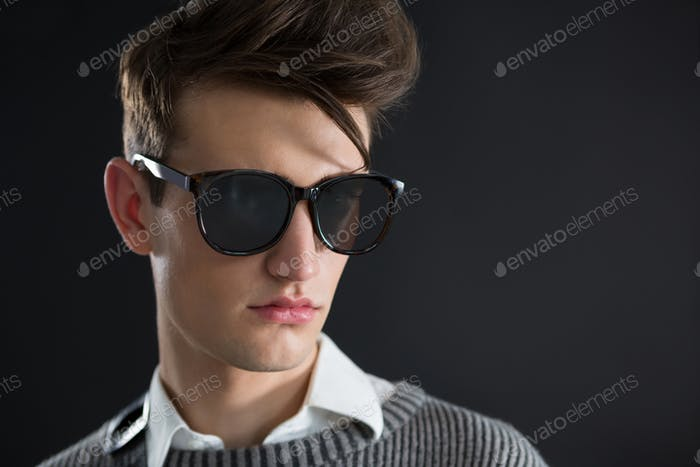 Androgynous man in sunglasses posing against black background