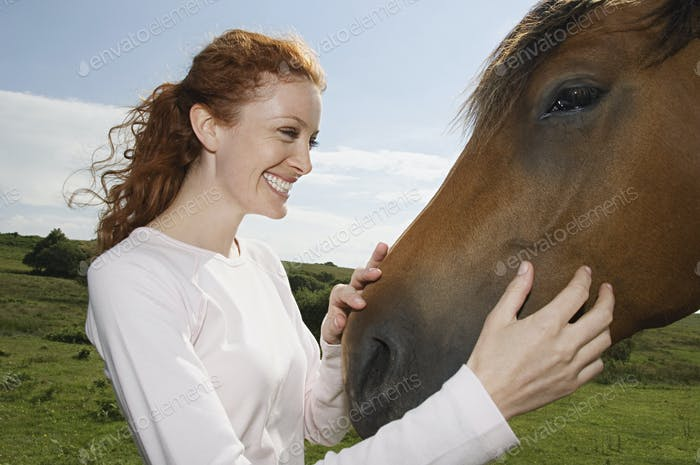 A young woman stroking the muzzle of a bay horse.