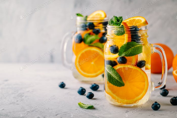 Infused detox water with orange, blueberry and mint. Ice cold summer coctail or lemonade.