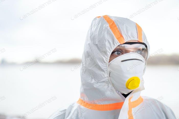 Frau mit Schutzanzug und Atemschutzmaske im Freien stehend, Coronavirus-Konzept