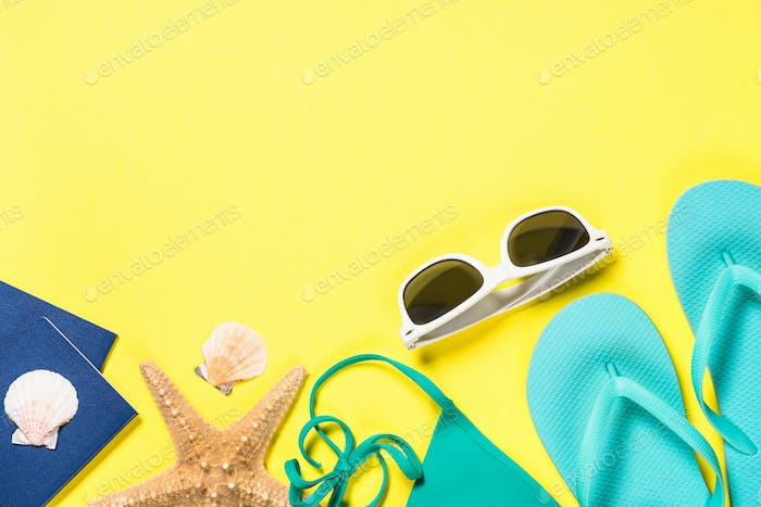Blue flip flops, swimsuit, sunglasses and starfish on yellow background