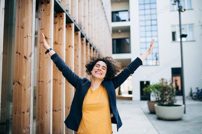 Eine junge Geschäftsfrau, die draußen steht, Spannung zum Ausdruck bringt