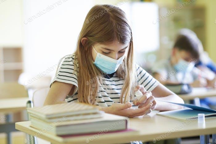 Schoolgirl cleaning hands with disinfecting antibacterial spray