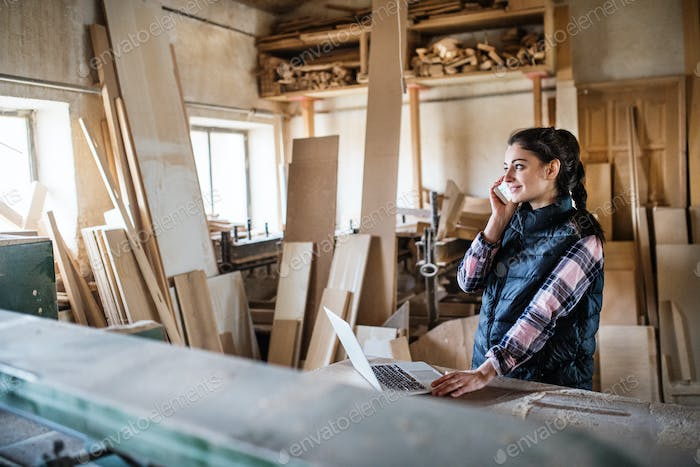 A woman worker with smartphone and laptop in the carpentry workshop.