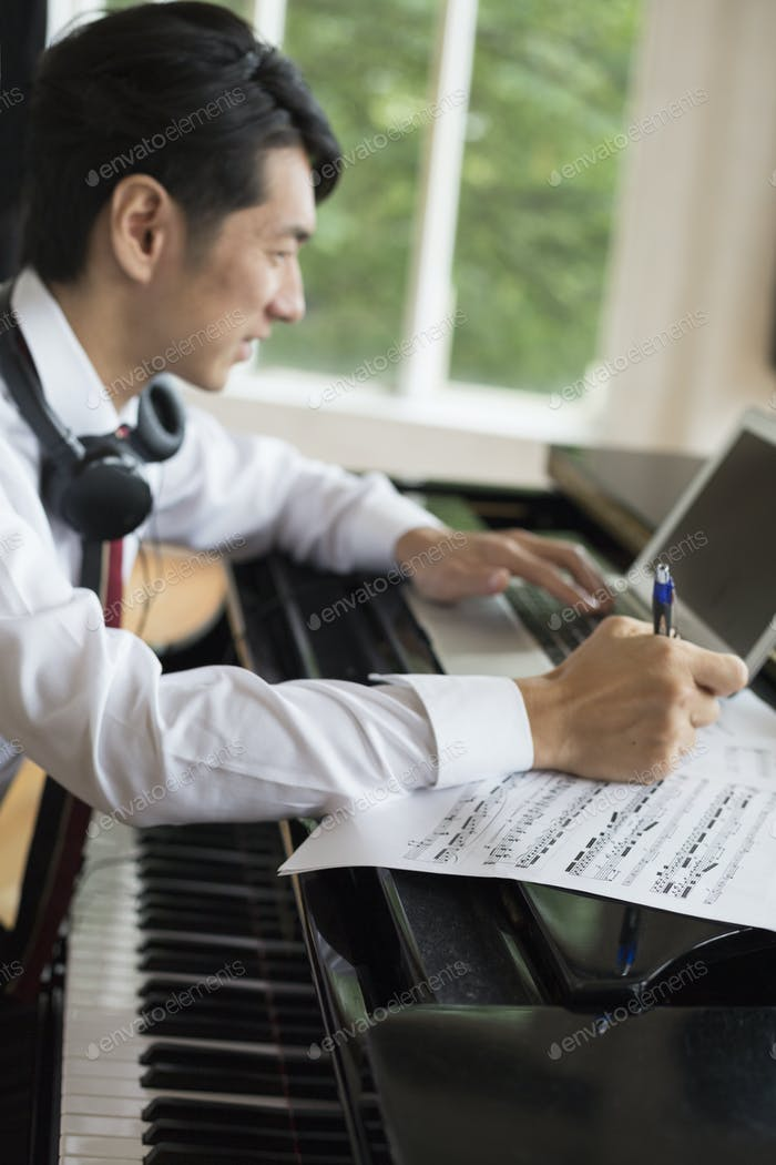 Young man sitting at a grand piano in a rehearsal studio, annotating sheet music.
