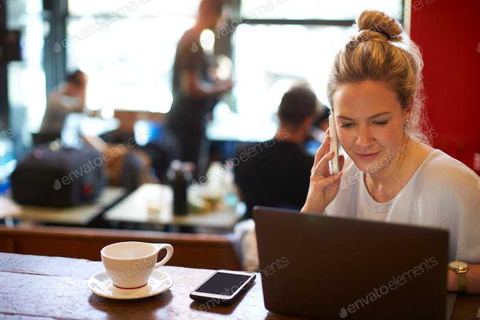 Woman In Coffee Shop Working On Laptop And Using Mobile Phone