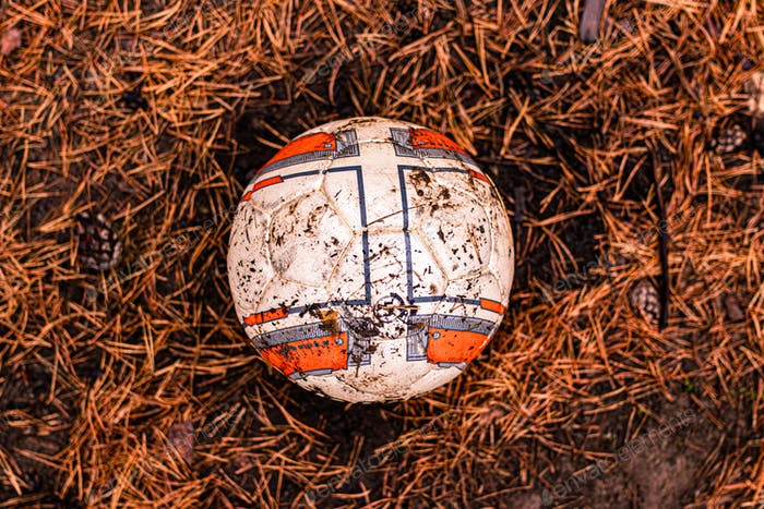 Dirty abandoned soccer ball in the woods. forgotten. lost. old.