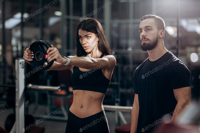 Athletic girl doing exercise for the muscles of the arms with weight in the gym under the