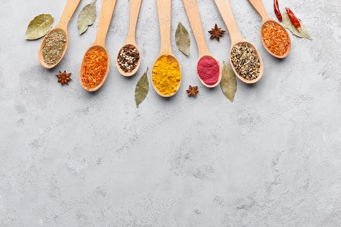 Mix of spices in wooden spoons, top view