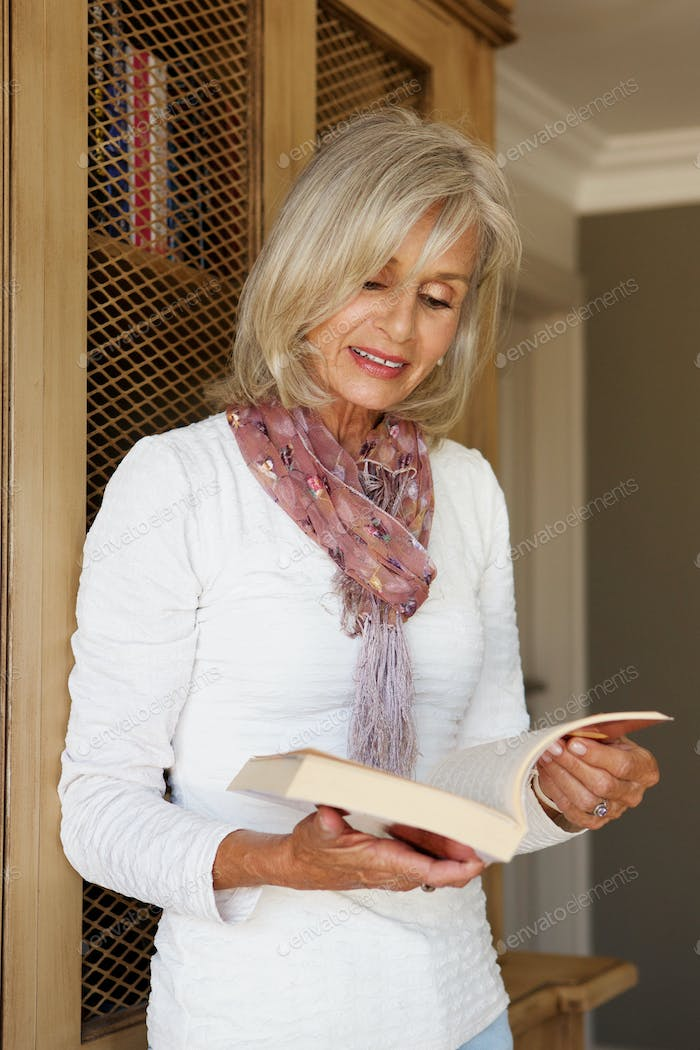 beautiful older woman in study reading book