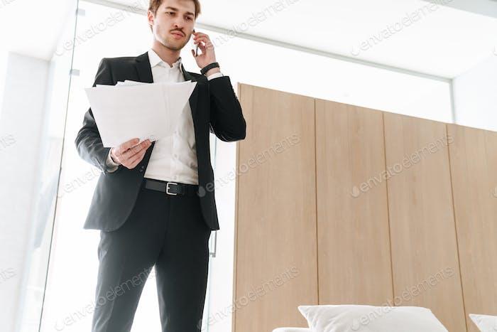 Foto von ernsthaften Geschäftsmann hält Dokumente und spricht auf Handy