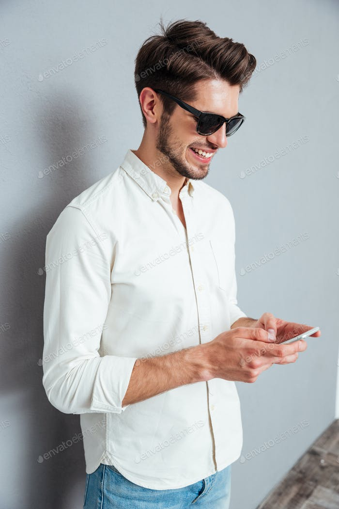 Happy attractive young man in sunglasses standing and using smartphone