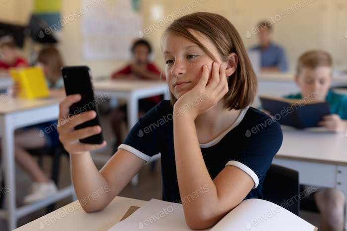 Schoolgirl sitting at a desk in an elementary school classroom using a smartphone