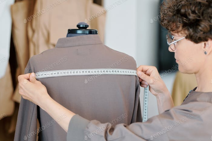 Young female tailor measuring back width of grey jacket on mannequin