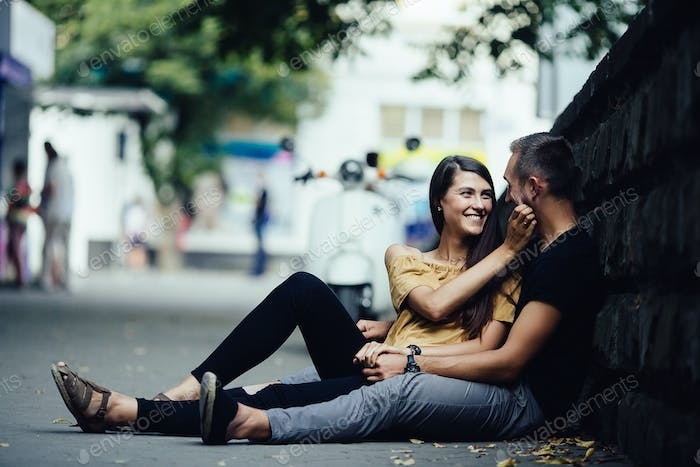 young beautiful couple sitting on the ground