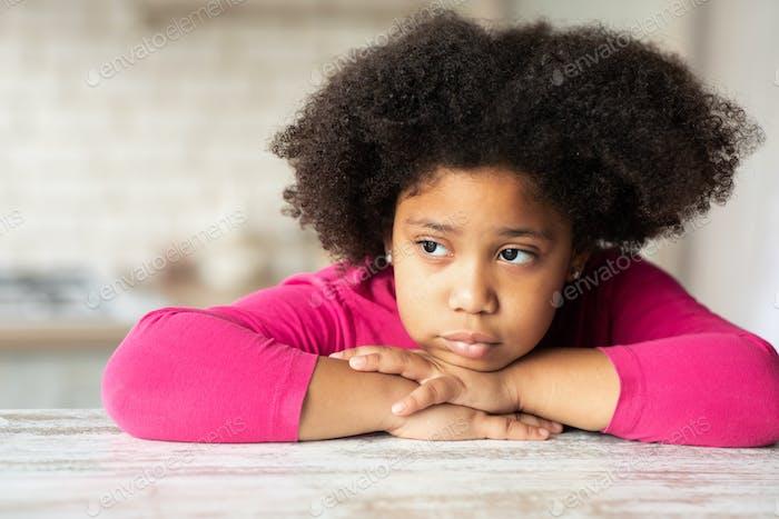 Porträt eines süßen, traurigen kleinen schwarzen Mädchens, das am Tisch in der Küche