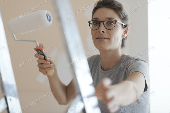 Happy woman painting walls in her new apartment