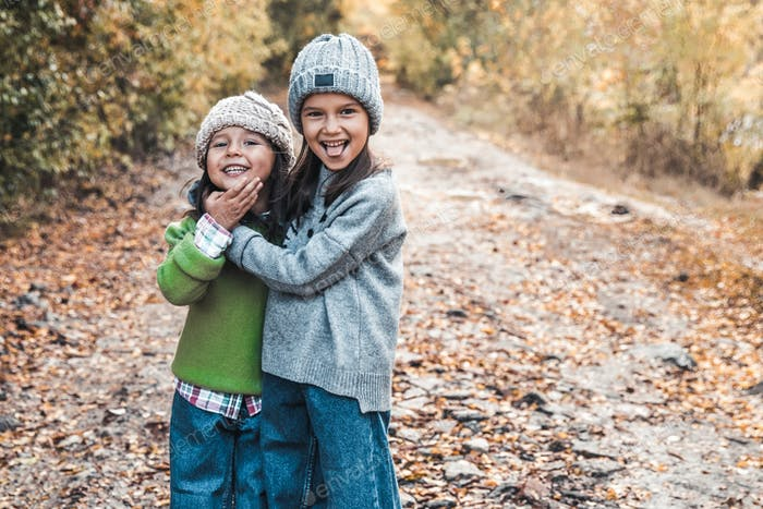 Kleine Mädchen lächeln und genießen das Leben an einem Herbsttag, Freundschaft, Schwestern, Beziehungen, Familie