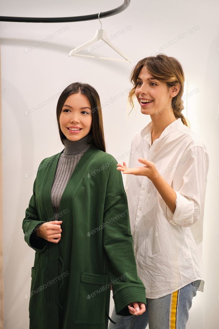 Young fashion consultant joyfully helping trying on cardigan to beautiful Asian girl in store