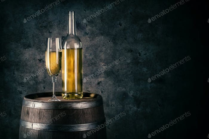 Bottle and glass of white wine on wooden barrel