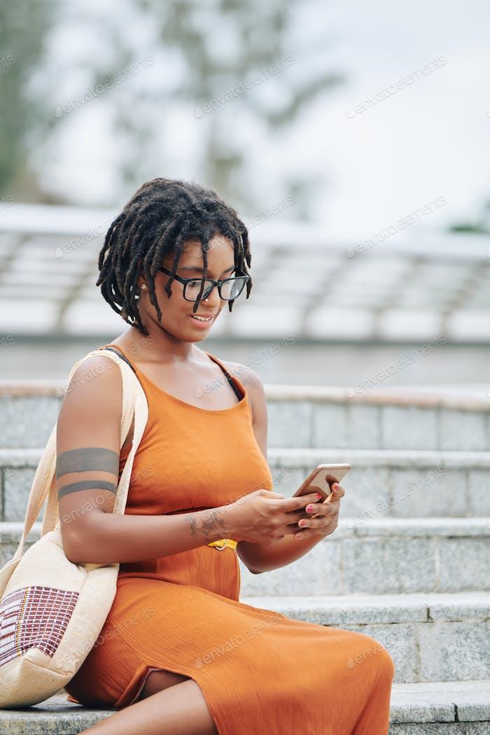 Frau sitzt auf der Treppe mit Telefon
