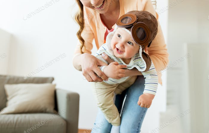 happy mother with baby wearing pilot hat at home