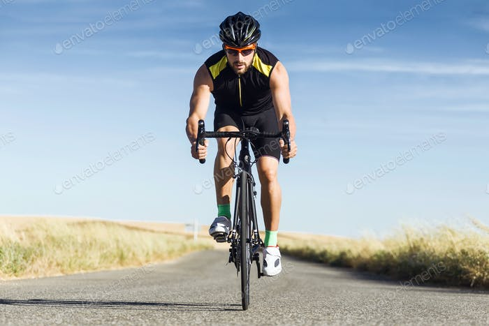 Handsome young man cycling on the road.