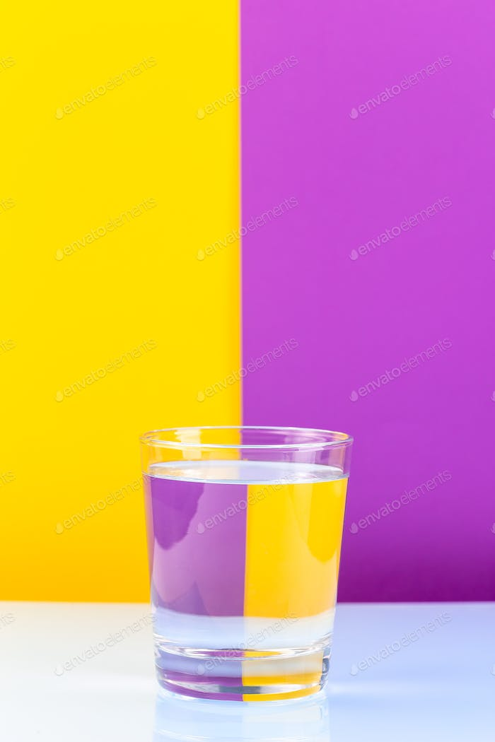 Optical illusion with glass of water and colorful paper