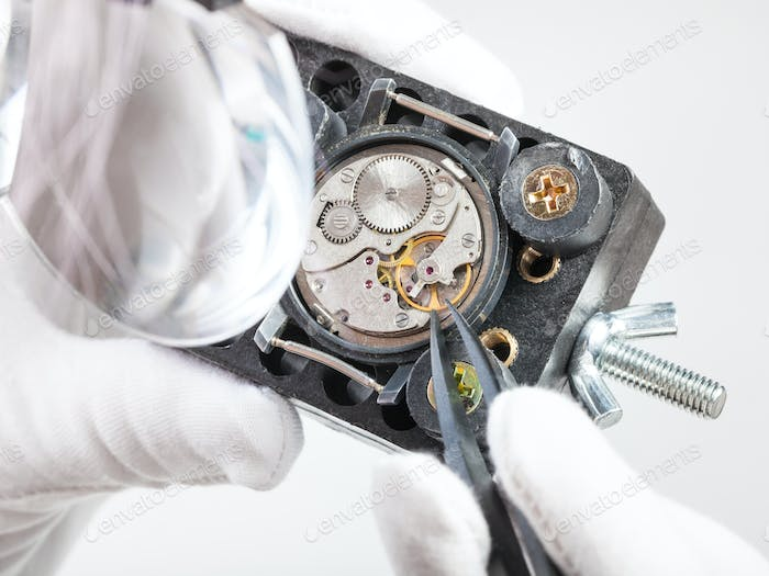 watchmaker in magnifier repairs wristwatch