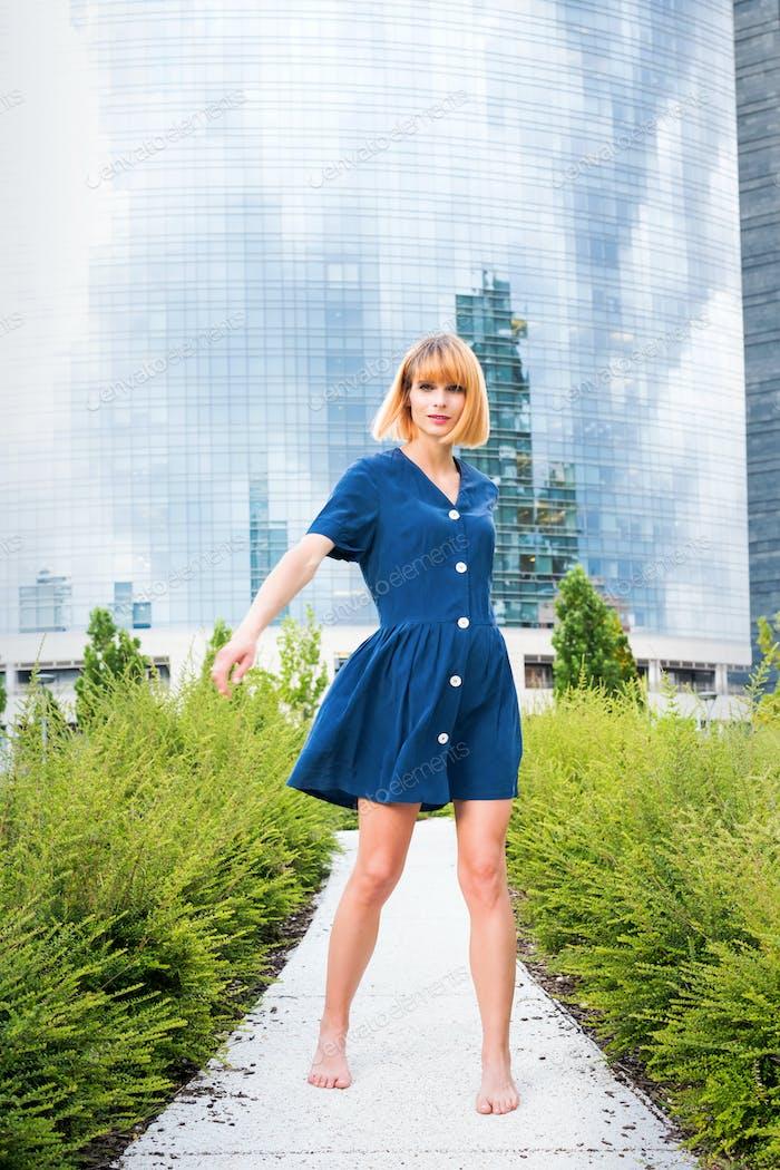 Despreocupada mujer atractiva descalza bailando en el centro de la ciudad