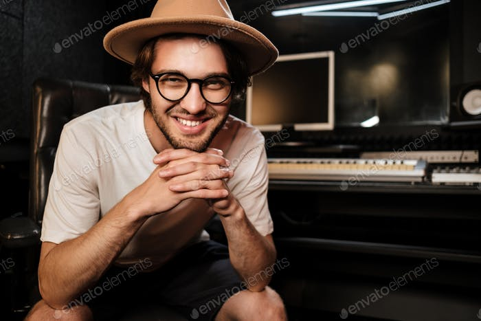 Attractive smiling guy joyfully posing on camera in sound recording studio
