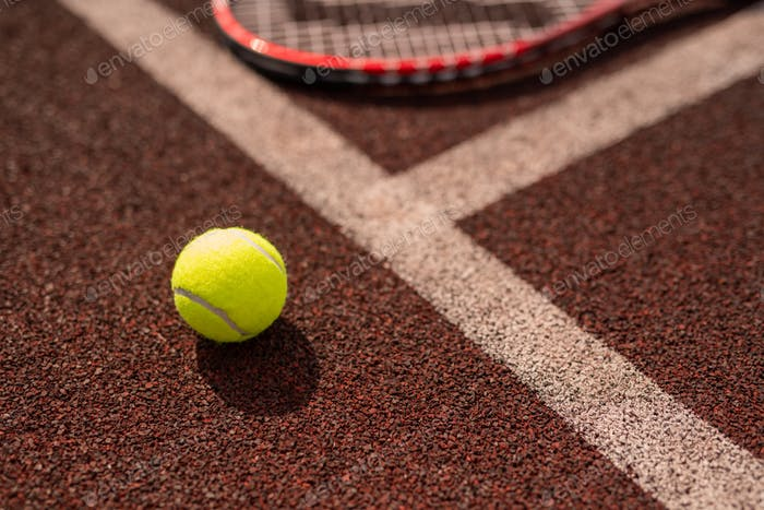 Yellow tennis ball by white line of sports playground